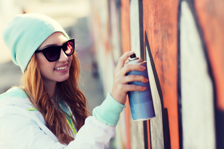 Foto de people, art, creativity and youth culture concept - young woman or teenage girl drawing graffiti with spray paint on street wall - Imagen libre de derechos