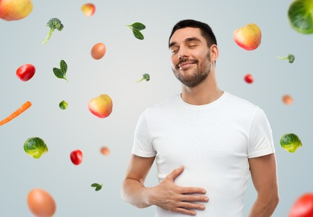 Photo pour food, healthy eating, diet and people concept - happy full man touching his tummy over gray background with falling fruits - image libre de droit