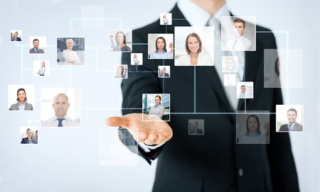 Foto de people, business, technology, headhunting and cooperation concept - close up of man hand showing business contacts icons projection - Imagen libre de derechos