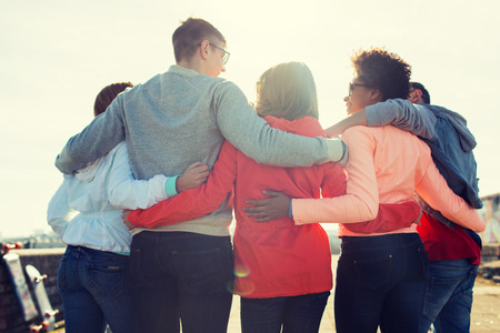 Photo for tourism, travel, people, leisure and teenage concept - group of happy friends hugging and talking on city street from back - Royalty Free Image
