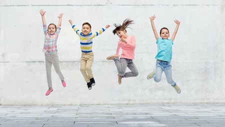 Foto de happiness, childhood, freedom, movement and people concept - happy little girl jumping in air over concrete wall on street background - Imagen libre de derechos