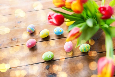 Foto de easter, holidays, tradition and object concept - close up of colored easter eggs and tulip flowers in bucket on wooden table over holidays lights - Imagen libre de derechos