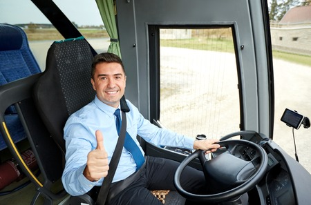 Photo pour transport, tourism, road trip and people concept - happy driver driving intercity bus and snowing thumbs up - image libre de droit