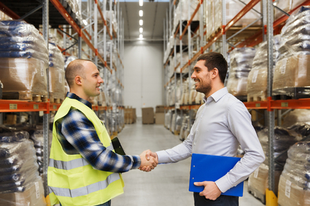 Photo pour wholesale, logistic, people and export concept - manual worker and businessmen with clipboard shaking hands and making deal at warehouse - image libre de droit