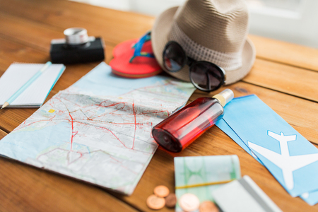 Foto de summer vacation, tourism and objects concept - close up of travel map, airplane tickets, money and personal accessories - Imagen libre de derechos