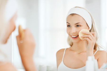 Photo pour beauty, skin care and people concept - smiling young woman washing her face with facial cleansing sponge at bathroom - image libre de droit
