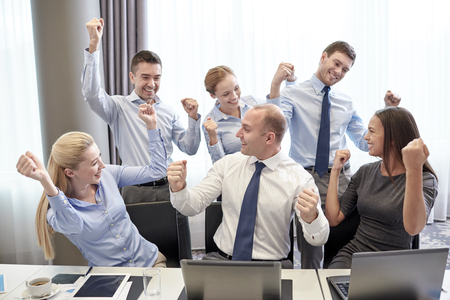Foto de business, people, technology, gesture and teamwork concept - smiling business team raising hands and celebrating victory in office - Imagen libre de derechos