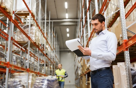 Photo pour wholesale, logistic, people and export concept - businessman or supervisor with clipboards at warehouse - image libre de droit