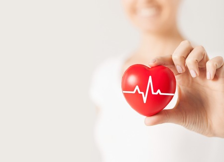 Foto de health, medicine, people and cardiology concept - close up of happy woman with cardiogram on small red heart - Imagen libre de derechos