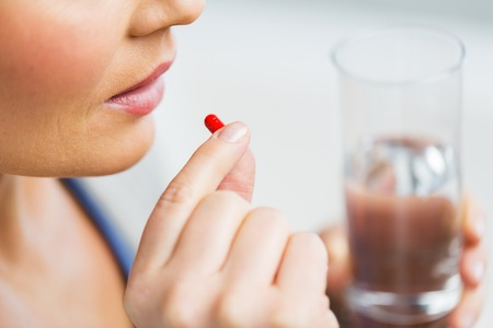 Photo pour medicine, health care and people concept - close up of woman taking in pill - image libre de droit