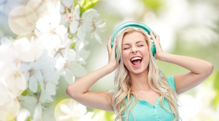 Photo for music, technology and people concept - happy young woman or teenage girl with headphones singing song over natural spring cherry blossom background - Royalty Free Image