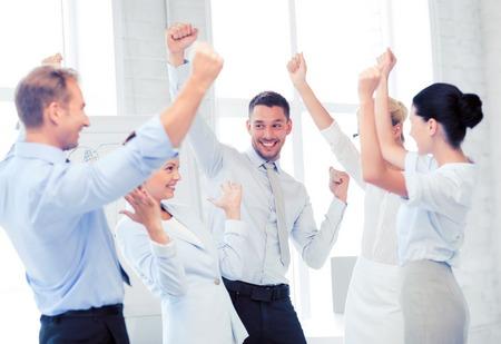 Foto de picture of happy business team celebrating victory in office - Imagen libre de derechos