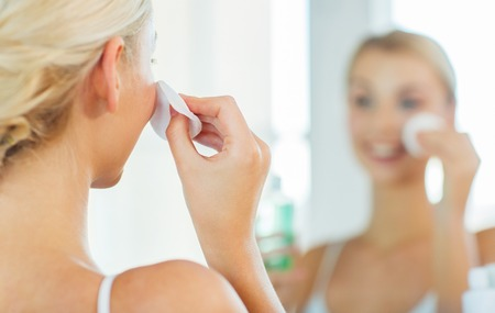 Foto de beauty, skin care and people concept - close up of smiling young woman cleaning her face with cotton disc and lotion at bathroom - Imagen libre de derechos
