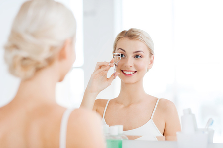 Photo pour beauty, make up, cosmetics, morning and people concept - smiling young woman with curler curling eyelashes and looking to mirror at home bathroom - image libre de droit