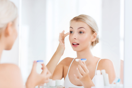 Photo for beauty, vision, eyesight, ophthalmology and people concept - young woman putting on contact lenses at mirror in home bathroom - Royalty Free Image
