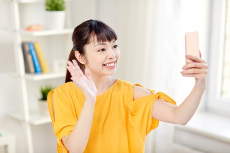 Photo pour people, technology and leisure concept - happy young asian woman taking selfie on smartphone at home and waving hand - image libre de droit