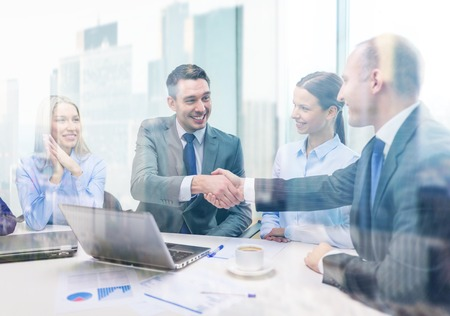 Photo for business, technology and office concept - two smiling businessman shaking hands in office - Royalty Free Image
