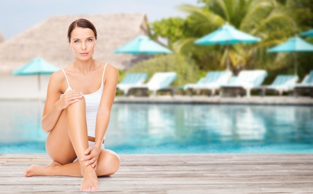 Photo pour people, beauty and summer holidays concept - beautiful young woman in cotton underwear touching her legs over exotic hotel resort beach with swimming pool and sunbeds background - image libre de droit