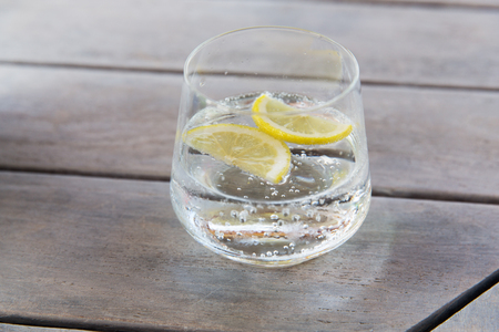 Photo for drink and refreshment concept - glass of sparkling water with lemon slices on table - Royalty Free Image