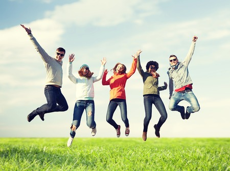 Foto de people, freedom, happiness and teenage concept - group of happy friends in sunglasses jumping high over blue sky and grass background - Imagen libre de derechos