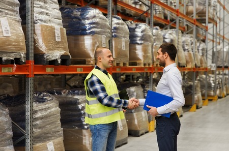 Photo for wholesale, logistic, people and export concept - manual worker and businessmen with clipboard shaking hands and making deal at warehouse - Royalty Free Image
