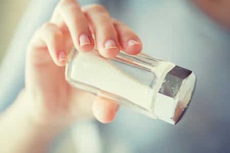 Photo pour close up of hand holding white salt cellar - image libre de droit