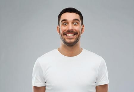 Foto de expression and people concept - man with funny face over gray background - Imagen libre de derechos