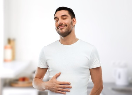 Foto de eating, satisfaction and people concept - happy full man touching his tummy over kitchen background - Imagen libre de derechos