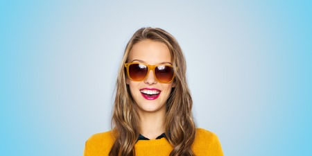 Photo pour people, style and fashion concept - happy young woman or teen girl face in sunglasses over blue background - image libre de droit