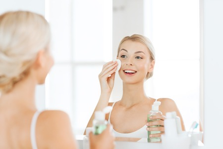 Photo pour beauty, skin care and people concept - smiling young woman applying lotion to cotton disc for washing her face at bathroom - image libre de droit