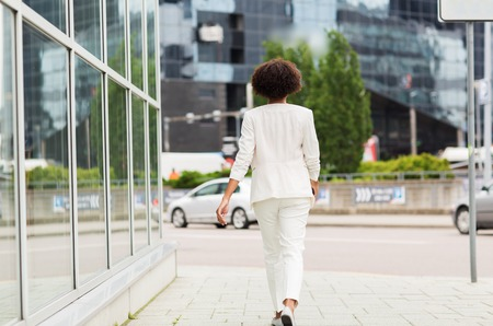 Photo for business and people concept - young african american businesswoman walking in city - Royalty Free Image
