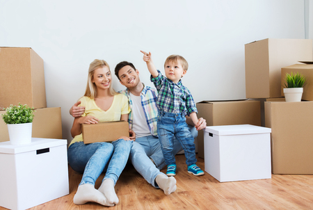 Photo pour mortgage, people, housing and real estate concept - happy family with boxes moving to new home - image libre de droit