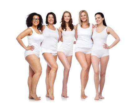 Foto de friendship, beauty, body positive and people concept - group of happy women different in white underwear - Imagen libre de derechos