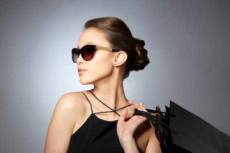 Foto für sale, fashion, people and luxury concept - happy beautiful young woman in black sunglasses with shopping bags over gray background - Lizenzfreies Bild