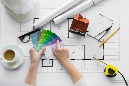 Foto de business, architecture, building, construction and people concept - close up of designer hands with color palette and house blueprint - Imagen libre de derechos