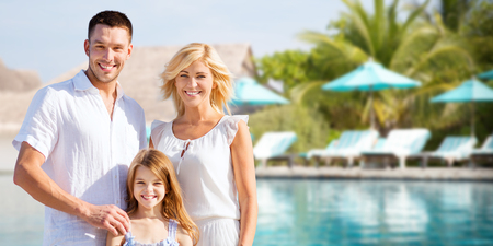 Photo for summer holidays, travel, tourism, vacation and people concept - happy family over hotel resort swimming pool and sun beds background - Royalty Free Image
