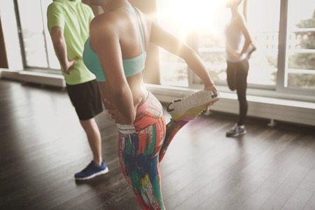 Foto de fitness, sport, training, gym and lifestyle concept - close up of people with trainer exercising and stretching leg in gym - Imagen libre de derechos