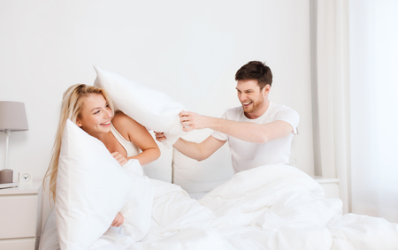 Photo pour people, family, fun, bedtime and fun concept - happy couple having pillow fight in bed at home - image libre de droit