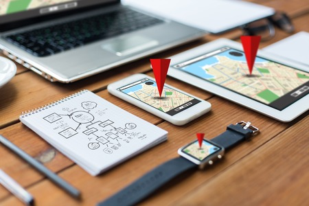 Foto per navigation, travel and technology concept - close up of laptop computer, tablet pc, notebook and smartphone with scheme and gps navigator map on wooden table - Immagine Royalty Free