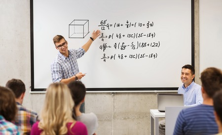 Foto de education, high school, mathematics and people concept - student standing with remote control in front of teacher and classmates and showing mathematical equalities on white board in classroom - Imagen libre de derechos