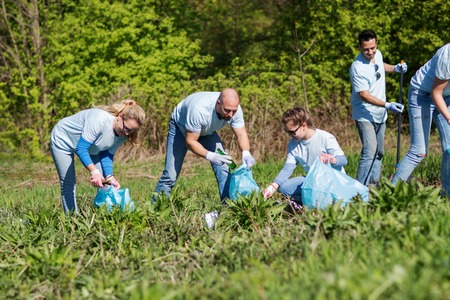 Photo for volunteering, charity, cleaning, people and ecology concept - group of happy volunteers with garbage bags cleaning area in park - Royalty Free Image
