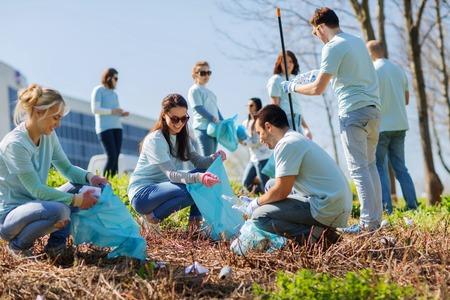 Foto de volunteering, charity, cleaning, people and ecology concept - group of happy volunteers with garbage bags cleaning area in park - Imagen libre de derechos