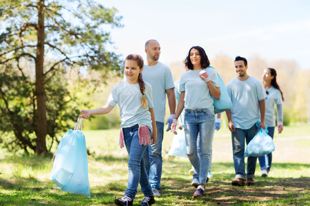 Photo for volunteering, charity, cleaning, people and ecology concept - group of happy volunteers with garbage bags walking in park - Royalty Free Image
