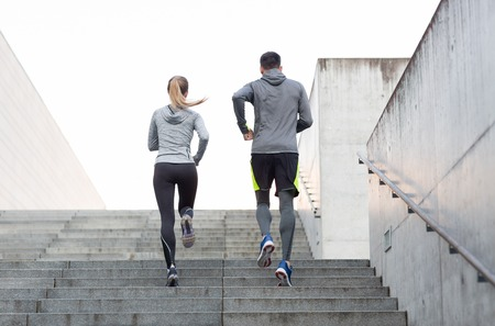 Foto de fitness, sport, people, exercising and lifestyle concept - couple running upstairs on city stairs - Imagen libre de derechos