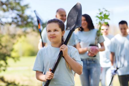 Foto de volunteering, charity, people and ecology concept - group of happy volunteers with tree seedlings and rake walking in park - Imagen libre de derechos