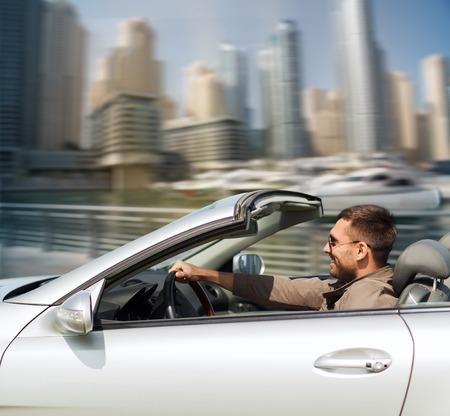 Foto de auto business, transport, leisure and people concept - happy man driving cabriolet car over dubai city port background - Imagen libre de derechos