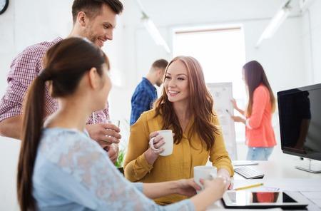 Foto de business, startup and people concept - happy creative team or students drinking coffee at office - Imagen libre de derechos