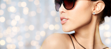 Photo for accessories, eyewear, fashion, people and luxury concept - close up of beautiful young woman in elegant black sunglasses over holidays lights background - Royalty Free Image