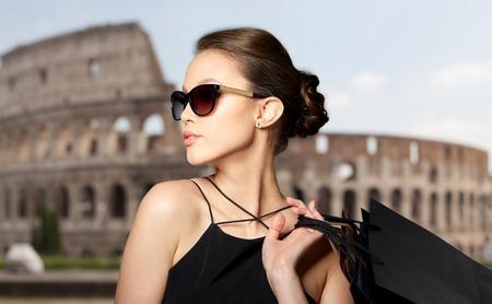 Foto de sale, tour, fashion, people and luxury concept - happy beautiful young woman in black sunglasses with shopping bags over coliseum background - Imagen libre de derechos