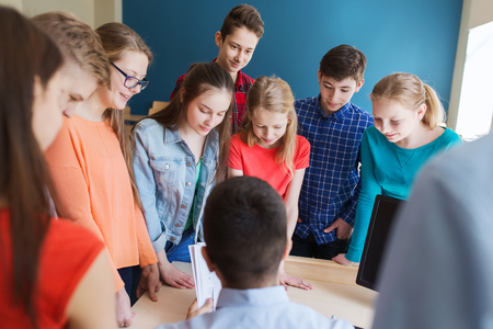 Photo for education, school, learning, teaching and people concept - group of students and teacher talking in classroom - Royalty Free Image